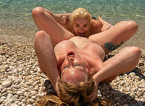 Horny British Milf with an increment of her young girlfriend enjoy each others pussies on the beach